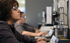 A row of Incision Lab employees working at their workstation.