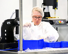A lab technician sterilizing equipment.