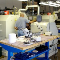 An employee sharping a medical device at his workstation.