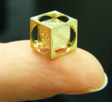 A small gold cube demonstrating Swiss machining.